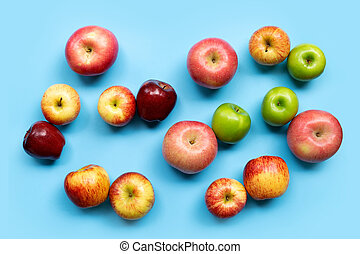 Variety of apples on blue background. Top view