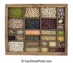 vintage, wooden typesetter case with variety of beans, lentils, peas, grains and seeds isolated with clipping path