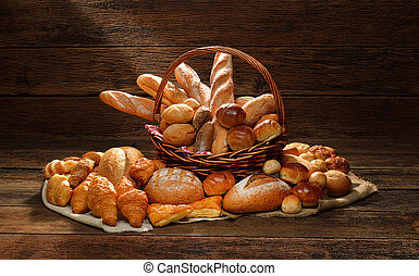 Variety of bread in wicker basket on old wooden background