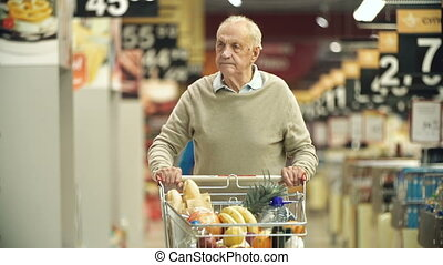 Senior man approaching camera walking along the market stalls