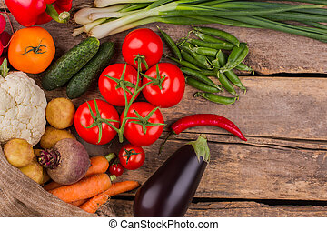Variety of different fresh vegetables on wood.