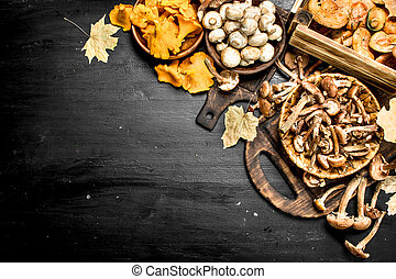 variety of forest mushrooms in boxes and bowls.