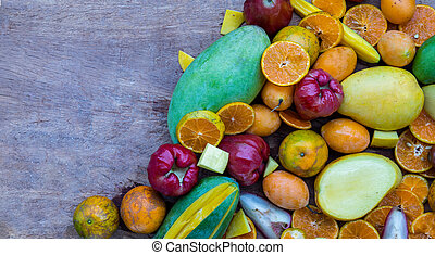 Variety of fresh assorted fruits on the old wooden table. Assorted fruits colorful background.