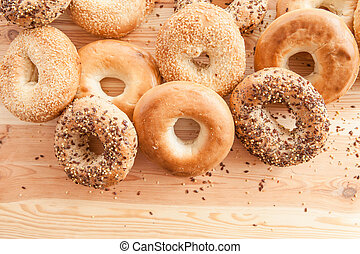 Variety of fresh bagels on rustic wooden background