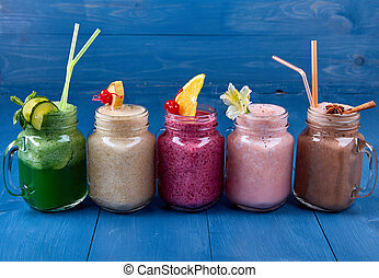 Variety of Fresh Healthy Paleo Smoothies and Cocktails in Rainbow Colors on Blue Wooden Background