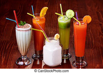 Variety of Fresh Healthy Paleo Smoothies and Cocktails in Rainbow Colors on Wooden Background, Beach Party