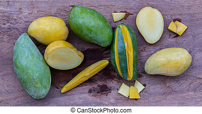 Variety of fresh mango on the old wooden table. fruits background.