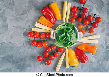 Variety of fresh organic tomato vegetables corn peppers and spinach in white Cup on beautiful background, top view, selective focus. Copy space