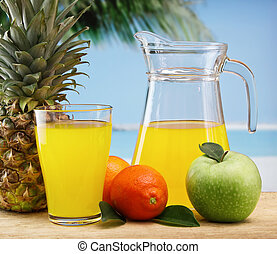 variety of fruit and juice on a beach table