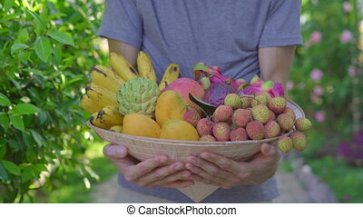 Variety of fruits in a Vietnamese hat. A man in a Vietnamese...