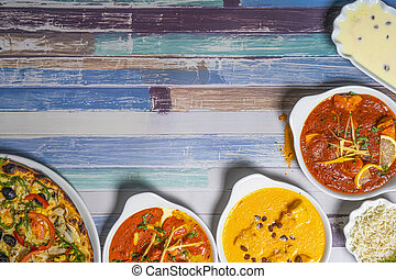 Variety of Indian dishes on vintage wooden background. Top view Copy space