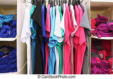 Variety of multicolored casual clothes in shop; T-shirts hang on racks and rolled into rolls