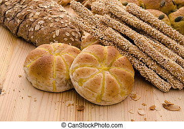 Variety of Organic Breads on plank background ,golden lights...