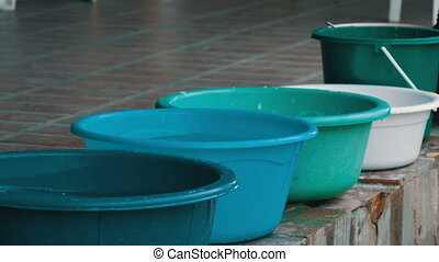 Variety of plastic basins with water standing on the street...