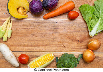 Variety of raw organic vegetables on wooden table