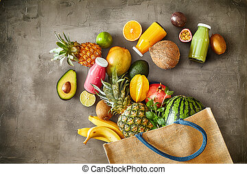 Large variety of ripe tropical summer fruit with juices overflowing from a full reusable fabric shopping bag onto textured slate in a concept of healthy ingredients for a vegetarian or vegan diet