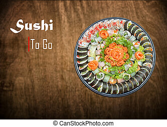 Variety of sushi rolls and sashimi on a plastic platter ...
