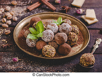Variety of sweet homemade chocolate pralines in the plate, selective focus