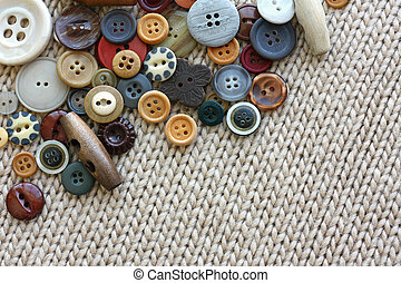 Variety of Vintage Buttons Scattered on Knit Fabric Background