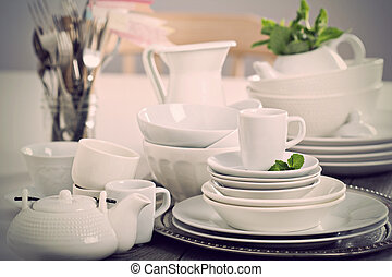 Variety of white dinnerware: plates, cups and bowls toned ...
