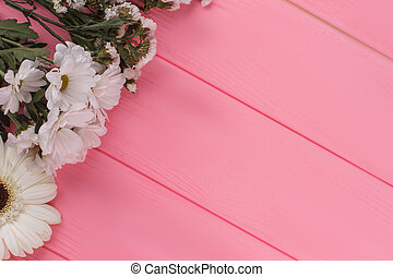 Variety of white flowers on wood and free space for text.