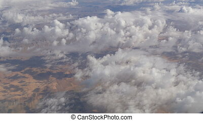 Variety of white fluffy clouds float across the sky, the...