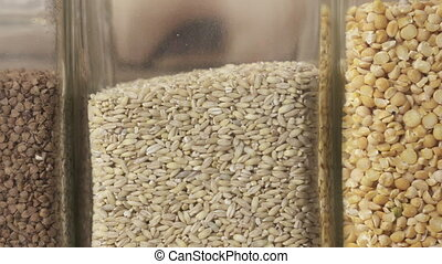 Variety of whole grains. Hand takes container with buckwheat...