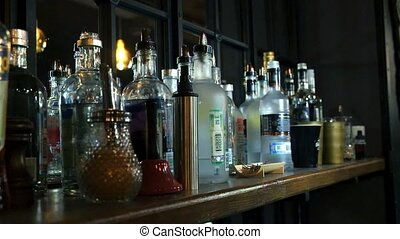 Various alcohol bottles in a bar, back light, all logos...