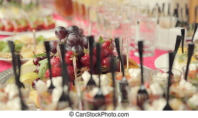 Various appetizers, desserts, drinks, vegetable salad at a banquet on catering