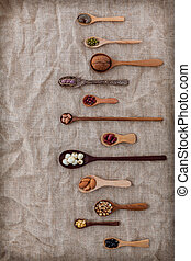 Various beans and nuts in the wooden spoon on brown cloth ...
