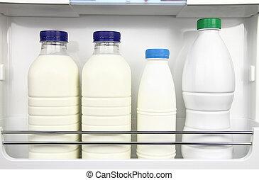 Various bottles of milk in the fridge