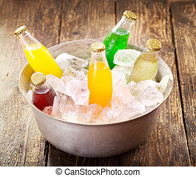 various bottles of soda in the bucket with ice