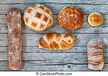 Various Bread Types On Wood Background
