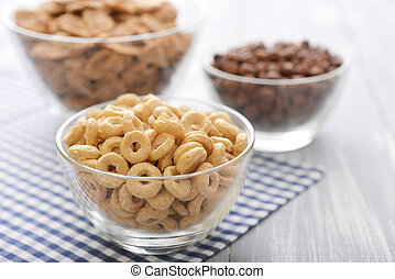 Various breakfast cereals in glass bowls on wooden background close-up