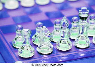 Various chess figures on  the glass chessboard