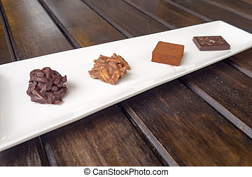 Various chocolates in white dish on wood table.