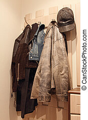 Various clothes hanging on coat rack.