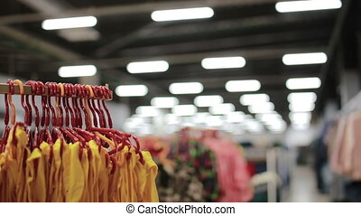 Various clothes on hangers in a store. slider shot