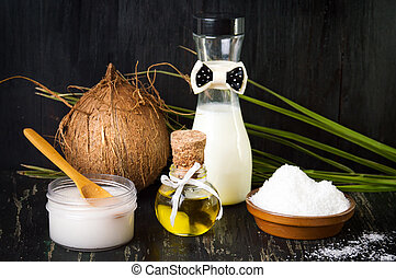 Various coconut products on black background