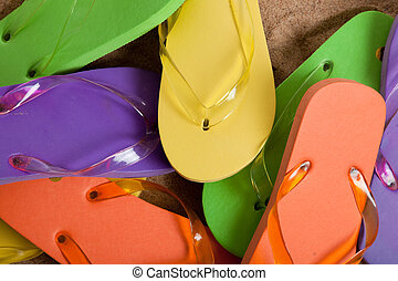 Various colored flipflops including yellow, green, orange and purple on sand