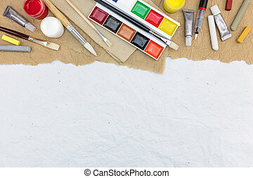 various colorful artistic drawing tools on recycled paper background