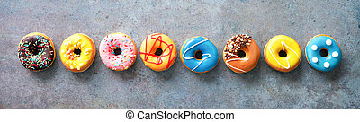 Various colourful donuts in a row on rustical grey background