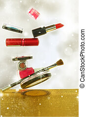 Various cosmetics in a glittery background