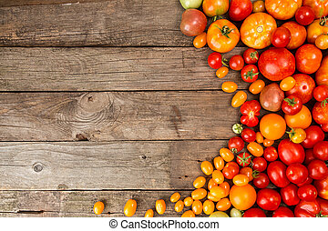 Various different color organic homegrown tomatoes on old wooden background. Background with red, yellow, orange and green tomatoes.