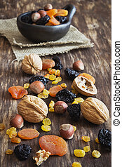 various dried fruits and nuts on an old wooden background....