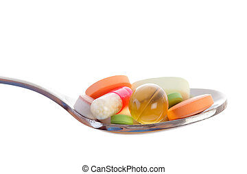 Various drugs vitamins and nutrition supplements on spoon.