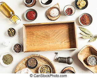 Various dry spices and sauces and wooden tray mock up on light background. Flat lay of small bowls with dijon mustard, olive oil, ketchup, capers and spices. Copy space. Top view