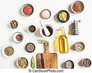 Various dry spices and sauces on a light background. Flat lay of small bowls with dijon mustard, olive oil, ketchup, capers and spices.