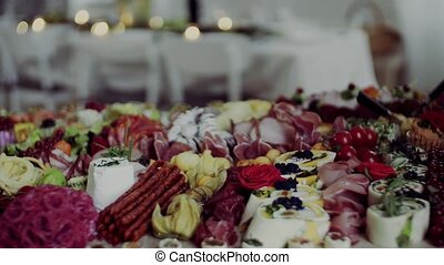 Various food and snacks on a tray on a indoor party, a cold...