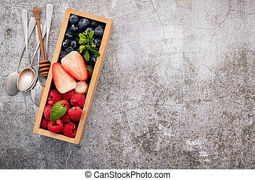 Various fresh berries blueberry, raspberry and strawberry in wooden box setup on concrete background .